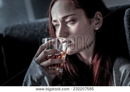 Cure For Sorrow. Frustrated Unhappy Sad Woman Spending Time In The Empty Room Looking Aside And Drin