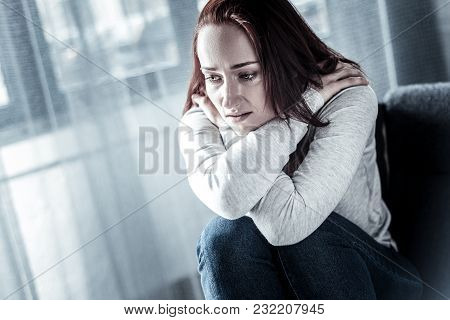 Im Stuck. Stressful Unhappy Lonely Woman Sitting In The Empty Hugging Herself And Looking Down.