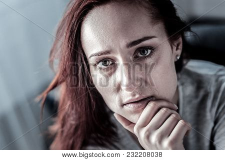 Real Problem. Redhead Stressful Upset Woman Sitting In The Empty Room Touching To Her Chin Looking S