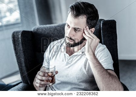 Need To Think. Deep Unshaken Serious Man Sitting In The Chair Holding A Glass And Drinking Alcohol.
