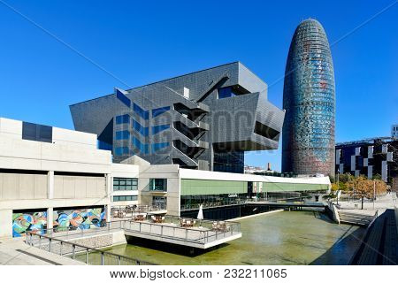 BARCELONA, SPAIN - MARCH 8, 2018: The Disseny Hub Barcelona museum and the Torre Glories, formerly known as Torre Agbar, designed by the famous architect Jean Nouvel, in the background