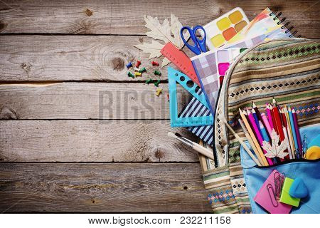 The School Bag With Stationery On Old Wooden Background