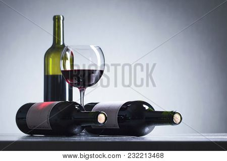 Bottles And Glass Of Red Wine . Old Paper Label . Copy Space For Your Text.