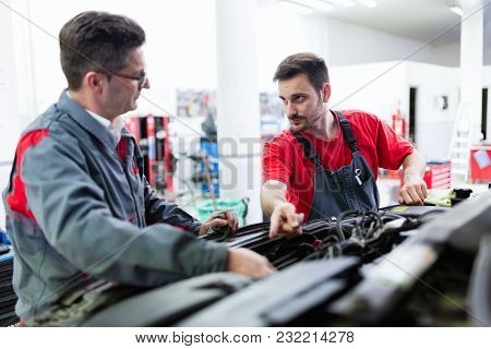 Car Mechanics Working At Automotive Service Center Together