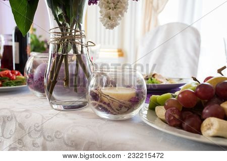 Beige Candle In A Glass Vase With Lilac Petals. Wedding Decor On The Table At The Newlyweds