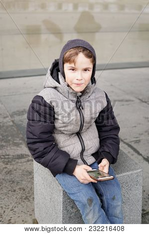 7 Year Old Boy With Smartphone Mobile Cell Phone Sitting Outside Alone On City Street In Winter
