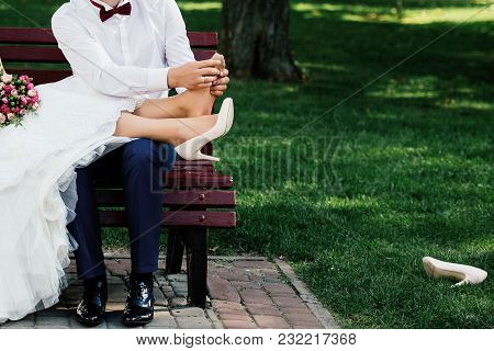 Wedding Couple Sitting On Bench And Relaxing In Park Outdoors, Copy Space. Groom Doing Foot Massage