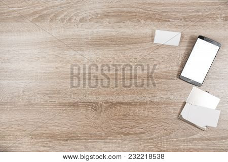 Top View On Wooden Desk With Smartphone With Empty Copy Space, Blank White Name Tag And Blank White