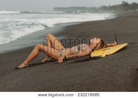 Girl In Swimsuit Resting On Beach Shore With Surf Board
