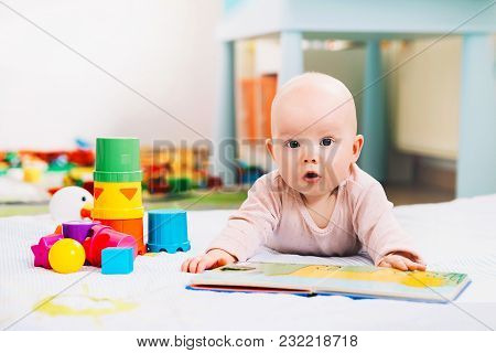 Adorable 6 Months Old Baby Looking And Reading A Book. Baby Playing With Colorful Toys At Home. Happ