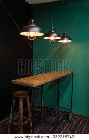Bar Rack On Wheels In The Kitchen With Hanging Lights And Wooden Bar Stools Against The Backdrop Of