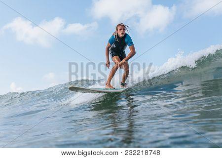 Man With Dreadlocks Riding Wave On Surf Board In Ocean
