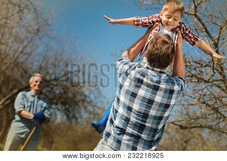 My Dear. Pleasant Loving Father Holding His Little Son In The Air And Resting Outdoors While A Posit