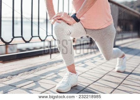 For My Health. Aged Athletic Concentrated Woman Training On The Quay Stretching Legs And Doing Exerc