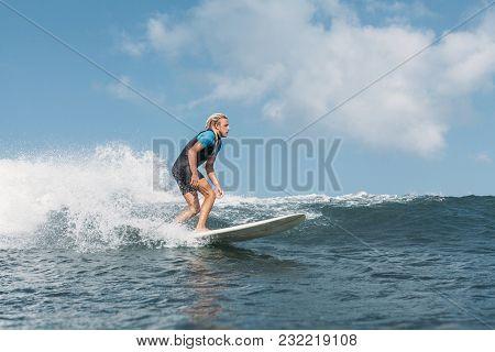 Male Surfer Riding Wave On Surf Board In Ocean