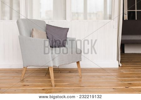 Interior Shot Of Simple Comfortable Armchair With Cushions On Wooden Floor