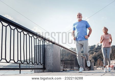 Follow Me. Confident Unshaken Athletic Man Spending Time On Fresh Air Looking Straight And Running A
