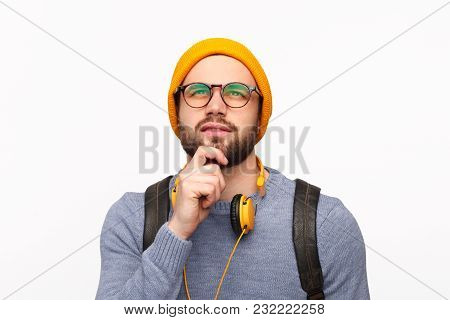 Young Bearded Man In Hat And Eyeglasses Wearing Headphones With Backpack Looking Away In Deep Though