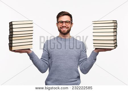 Young Cheerful Man Holding Stacks Of Books And Smiling At Camera Isolated On White.