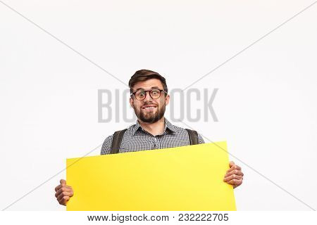 Handsome Smart Guy In Glasses And With Backpack Showing Yellow Empty Paper On White Background.
