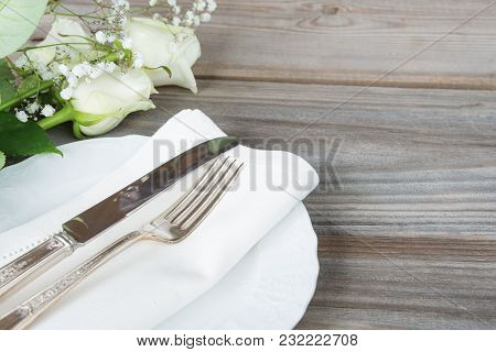 Beautiful Decorated Table With White Plates, Silverware And White Rose Flowers On An Old Wooden Tabl