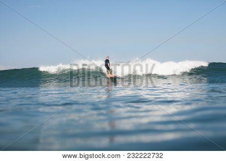 View Of Active Sportsman Surfing Wave In Ocean