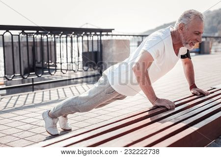 I Must To Do It. Strong Senior Persistent Man Being On The Quay Doing Exercises And Pushing From The