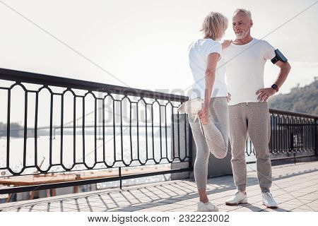Help Me Please. Handsome Confident Unshaken Man Standing On The Quay Smiling And Supporting A Woman.