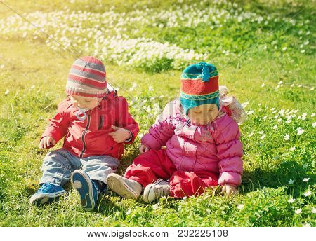 Little Boy And Girl In Hats Sitting On The Field With White Springflowers. Two Cute One Year Old Bab