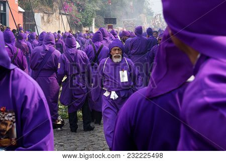 Antigua, Guatemala: March 18 2018: Older Purple Robed Man Along Crowed Of Purple Dressed Men At The