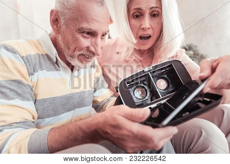 I Cant Believe In It. Interested Occupied Amazed Senior Couple Sitting Together In The Bright Room T