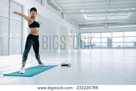 Fit Woman Exercising Yoga In Fitness Studio