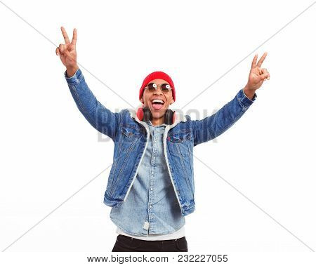 Ethnic Expressive Man With Headphones Showing Two Fingers Posing On White.