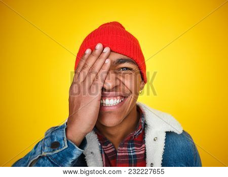 Headshot Of Cheerful Black Man In Hat Covering One Eye And Smiling Excitedly At Camera.