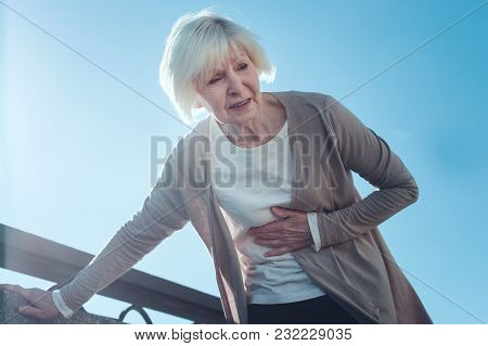 It Hurts So Much. Low Angle View On A Retired Woman Leaning On A Bridge Barrier While Feeling An Ext