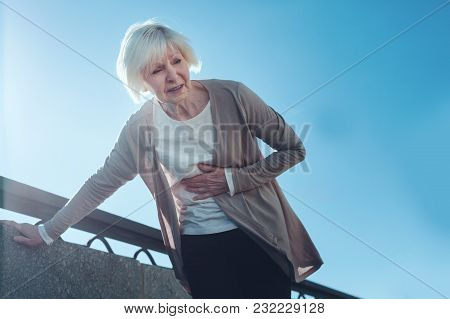 What A Pain. Low Angle Shot Of A Fearful Elderly Lady Suffering From A Severe Heart Pain And Bending