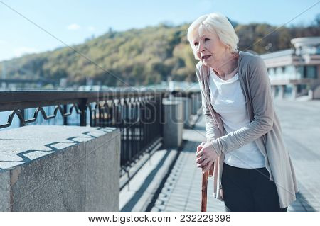 Fresh Air Is Healing. Emotionally Exhausted Retired Woman Leaning On A Walking Cane And Looking At A