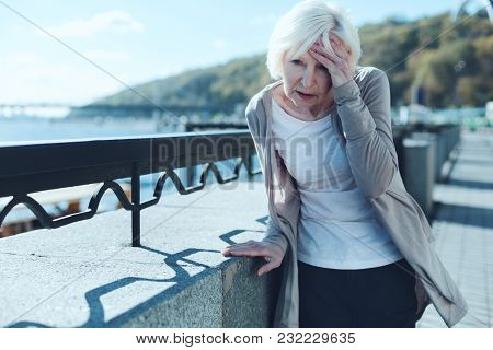 Need To Take My Pills. Exhausted Older Lady Leaning On A Barrier And Touching Her Forehead While Suf