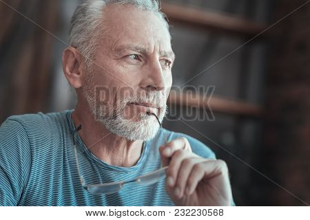 New Idea. Interested Deep Gray Haired Man Spending Time Alone Thinking And Holding The Glasses.