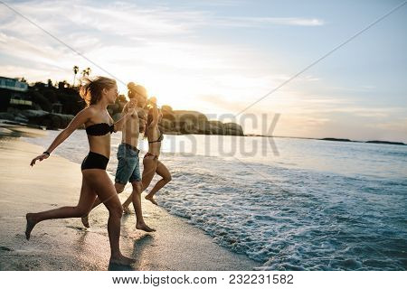 Group Of Happy Friends Running To The Sea On Sunset. Joyful Friends Having Fun On Summer Vacation At