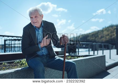 Stressful Life. Poor Older Man Leaning On A Walking Cane And Looking Into Vacancy While Feeling Some