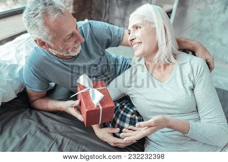 For My Beloved. Pleasant Aged Grey Haired Man Giving The Present To His Wife Smiling And Lying On Th
