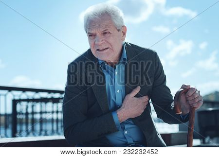It Hurts A Lot. Frustrated Senior Man Looking Into Vacant Space While Holding Her Hand On A Chest An