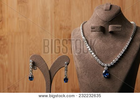 Women's diamond necklace made of platinum with a blue precious sapphire stone on a wooden background. Luxury female jewelry poster
