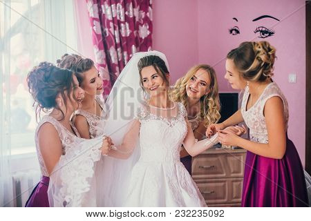 Beautiful Bridesmaids Help Put On Wedding Dress On Gorgeous Blonde Bride In Luxury Hotel Room Mornin