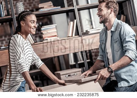New Life. Happy Cheerful Nice Couple Looking At Each Other And Smiling While Preparing For A New Lif