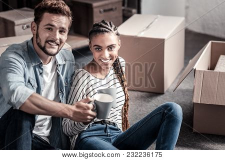 We Need A Break. Happy Joyful Nice Couple Sitting Together And Having Tea While Being Surrounded By