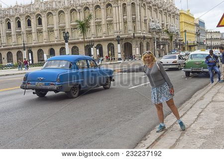 Havana, Cuba - January 04, 2018: A Girl Stretching Out Her Arm Stops A Taxi In The Square In Havana,