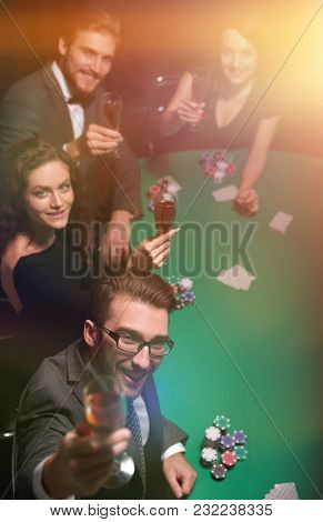 Group of young rich people is playing poker in the casino