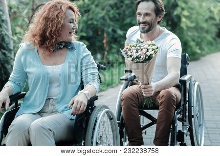 Hurry Up. Joyful Female Person Expressing Positivity And Sitting On The Wheelchair While Looking Sid